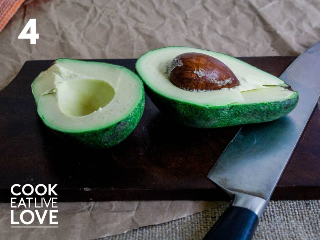 Open avocado with two halves is on cutting board with knife on the side.