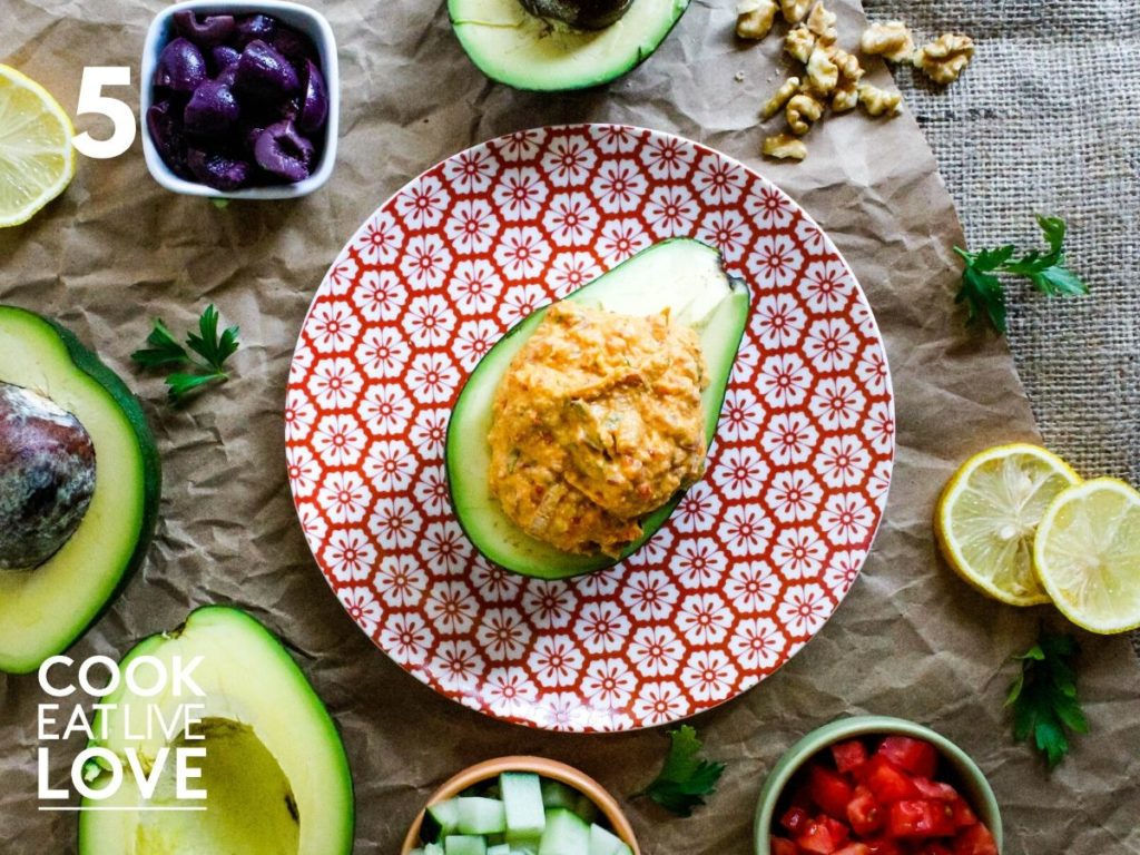 Avocado half filled with hummus is on a red and white plate atop a brown paper background.  Around the plate are the different toppings, lemon slices, parsley leaves and a whole avocado cut in half.