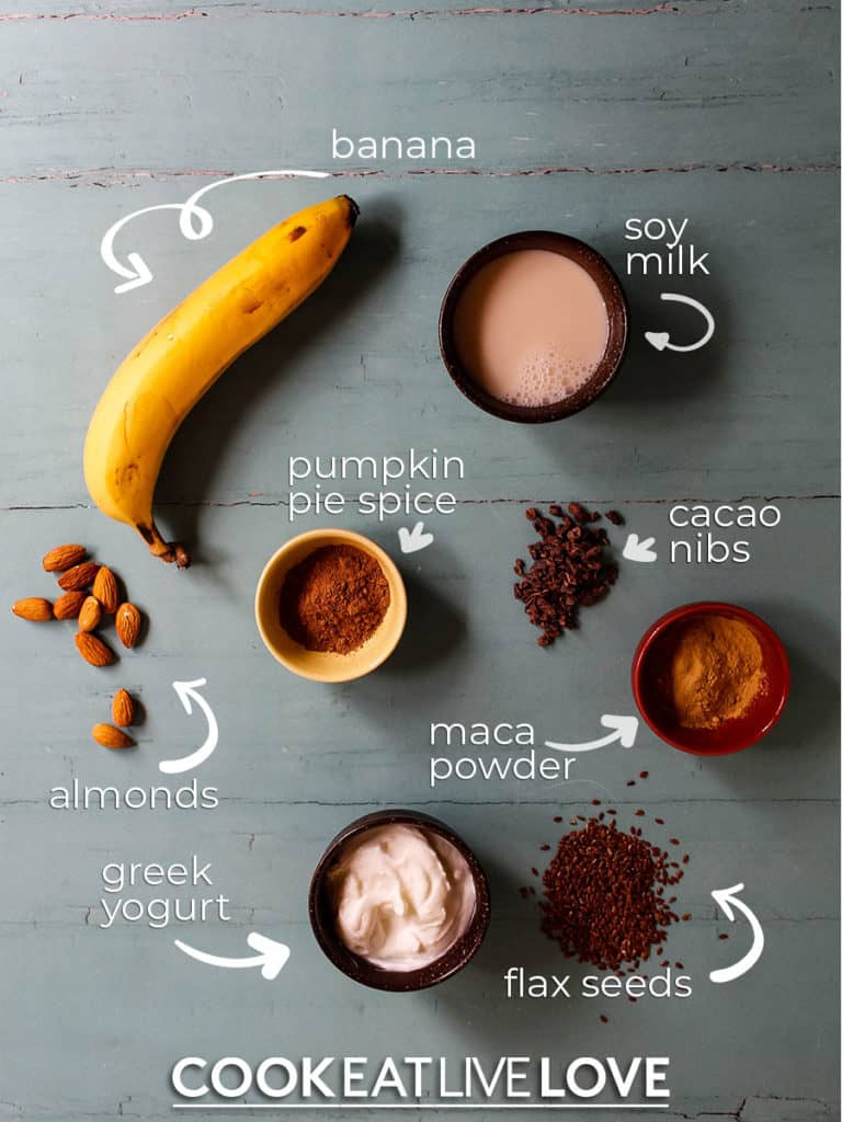 All the ingredients for a chocolate maca smoothie are laid out on a blue background.  Bananas, soy milk, cacao nibs, pumpkin pie spice, almonds, maca powder, flax and yogurt.  The names of the foods are also provided with arrows pointing to the foods in the picture.