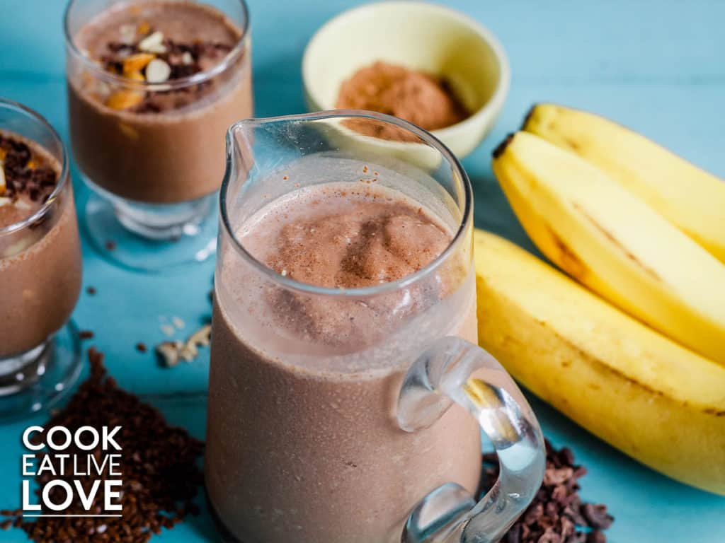 Close up of mini pitcher of superfood chocolate smoothie.  Around the pitcher are whole bananas, cacao nibs and powder as well as two smoothies in glasses ready to serve.