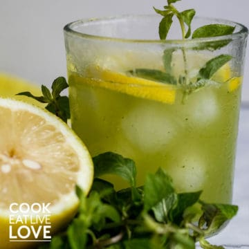 A closeup of glass of cucumber mint lemonade with some fresh mint and lemon half.