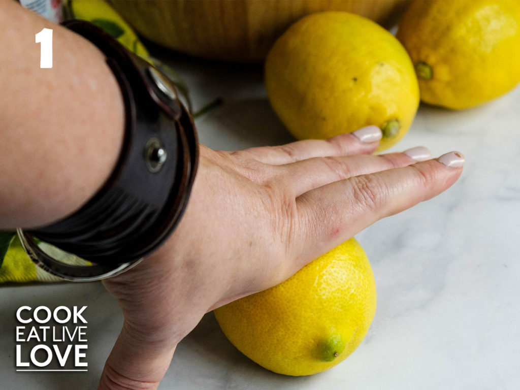 A hand in the picture is pressing down on one of the lemons to demonstrate the rolling of the lemons.