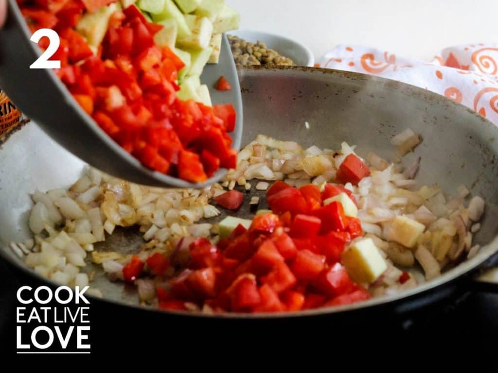 Cooked onions and garlic are in pan.  A bowl is shown adding in the red pepper, tomatoes and eggplant.