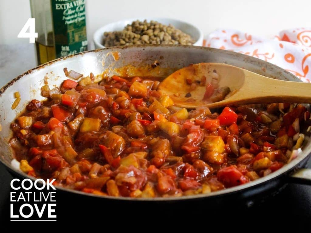 Cooking pan shows lentils, veggies and sauce mixed together with a wooden spoon.