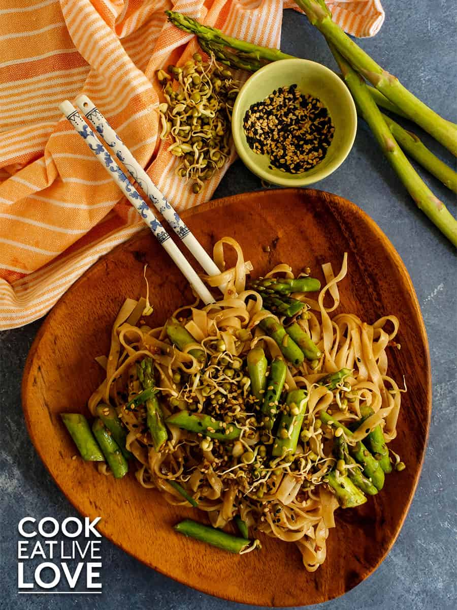 Vegetarian rice noodle stir fry served up on a wooden plate with white and blue ceramic chopsticks.  The plate is on a blue marble background.  Above the plate are ingredients from the dish, asparagus, sesame seeds and sprouts.