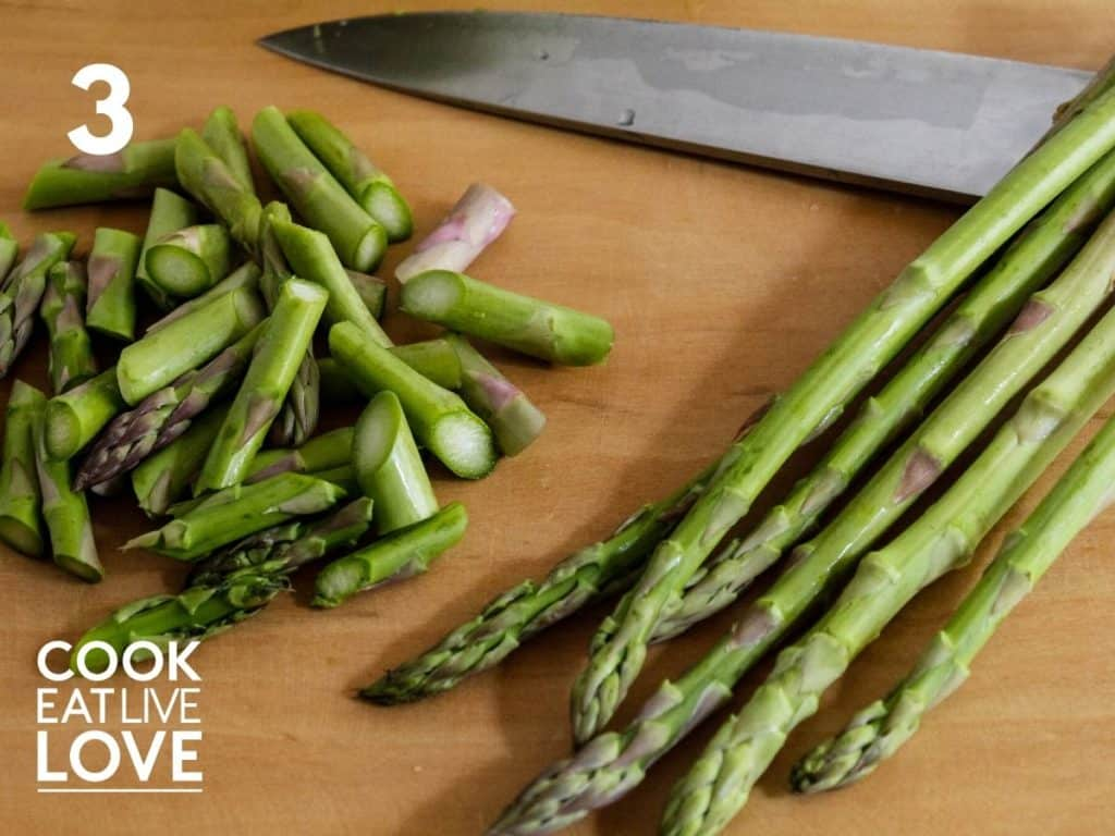 Asparagus stalks are laying on a wooden cutting board next to some asparagus already cut into one inch pieces using an angle cut.  Knife is laying above the asparagus.