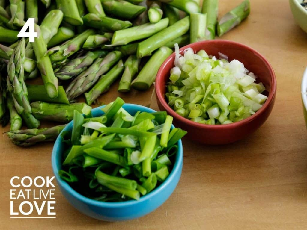 The green onion is cut keeping the white and green parts separately in small ceramic bowls set on a wooden cutting board.  The cut asparagus is also shown on the cutting board above the small bowls of onion.