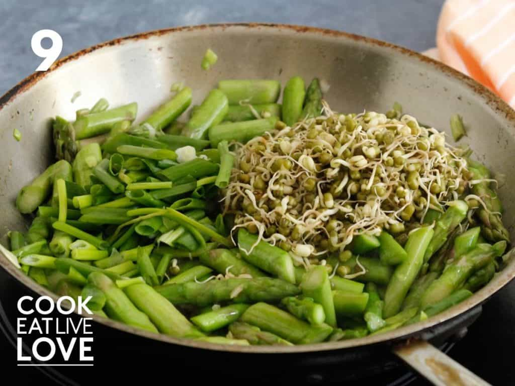Sprouts and green onion tops are added to the cooked asparagus and onion.