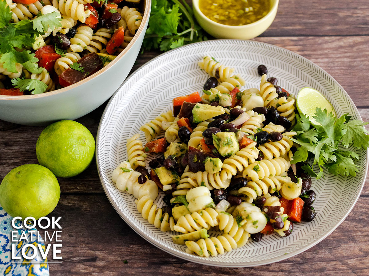 Southwest pasta salad on a white and gray plate.  To the left are some whole limes and above the bowl of pasta salad and the dressing.