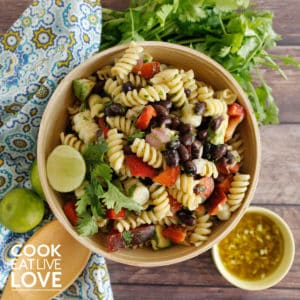 Bowl of easy vegan pasta salad is photoed from above. Dressing is to the bottom right and at the top are a blue and yellow napkin and the dressing.