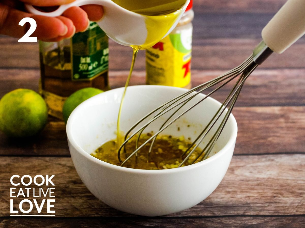 Oil is slowly being added to the dressing and the whisk is stirring in the bowl.
