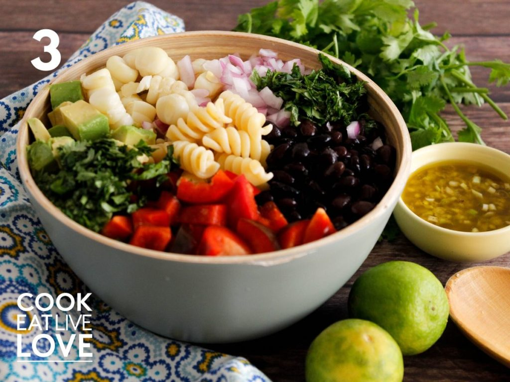 Ingredients for southwest pasta salad are shown in a bowl. Red bell pepper, cilantro, avocado, corn, red onion, and black beans.