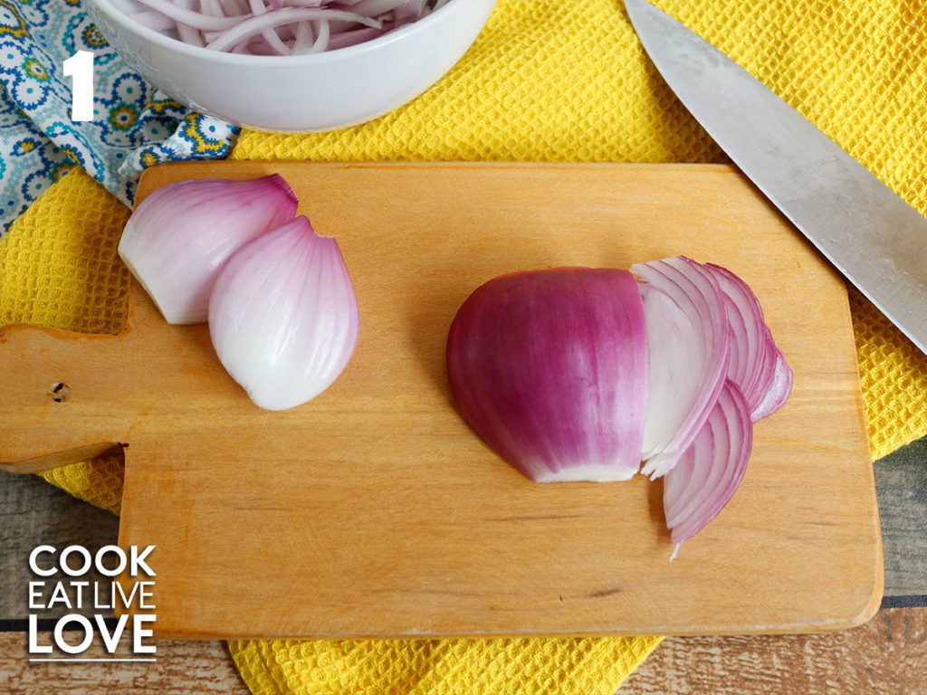Small wooden cutting board on yellow towel with onion half on top and knife to the side.