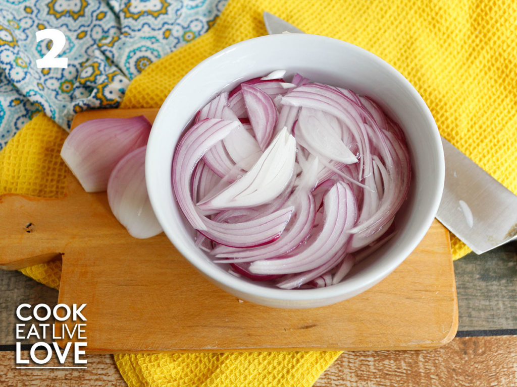 Onions are in a white bowl soaking in water shown on top of  a wooden background. With a knife off to the side and a yellow background.
