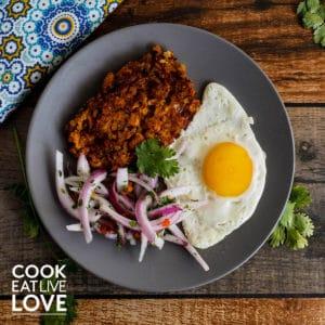 Plate of tacu tacu with fried egg and onions.