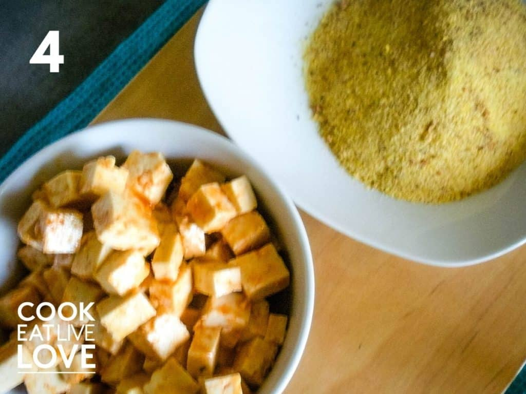 On a wooden background sits the bowl of marinated tofu and bowl of the cornmeal breading mixture.