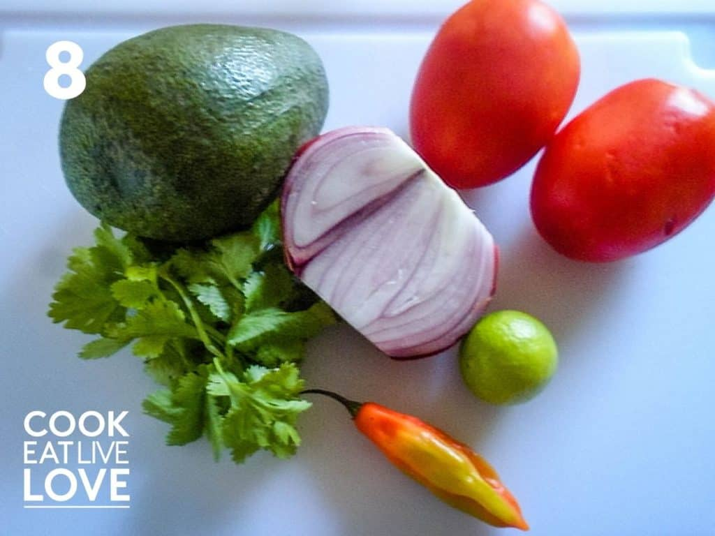 Tomato salsa ingredients are on the cutting board, tomatoes, red onion, lime, spicy chile, cilantro and avocado.