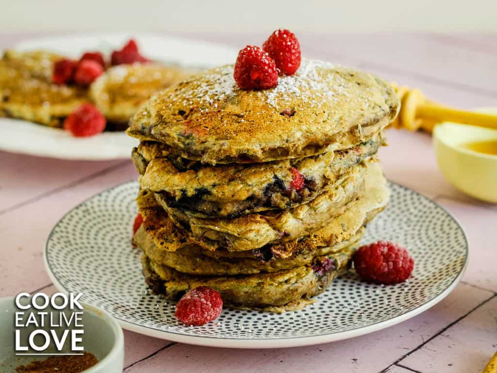 Stack of vegan chia pancakes on gray spotted plate garnished with fresh berries set on a pink wooden counter.  Behind are pancakes on plate with fork and syrup in a small bowl.
