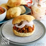 Sloppy joe on a plate with onions and buns behind