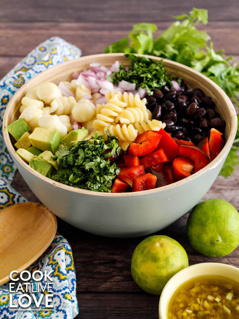 Photo of a bowl of pasta topped with black beans, red bell pepper, cilantro, avocado, corn and onion.