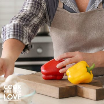 Hands cutting bell pepper on cutting board.
