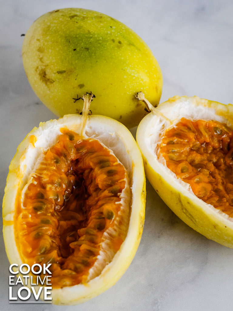 Fresh passionfruit on white marble background.  One whole in background and one cut in half open showing the orange pulp and dark seeds.