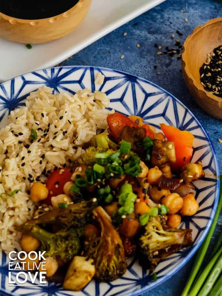 Overhead angle photo of final plate of teriyaki vegetables served up with rice.  Also in picture are a small bowl of extra sauce and sesame seeds.