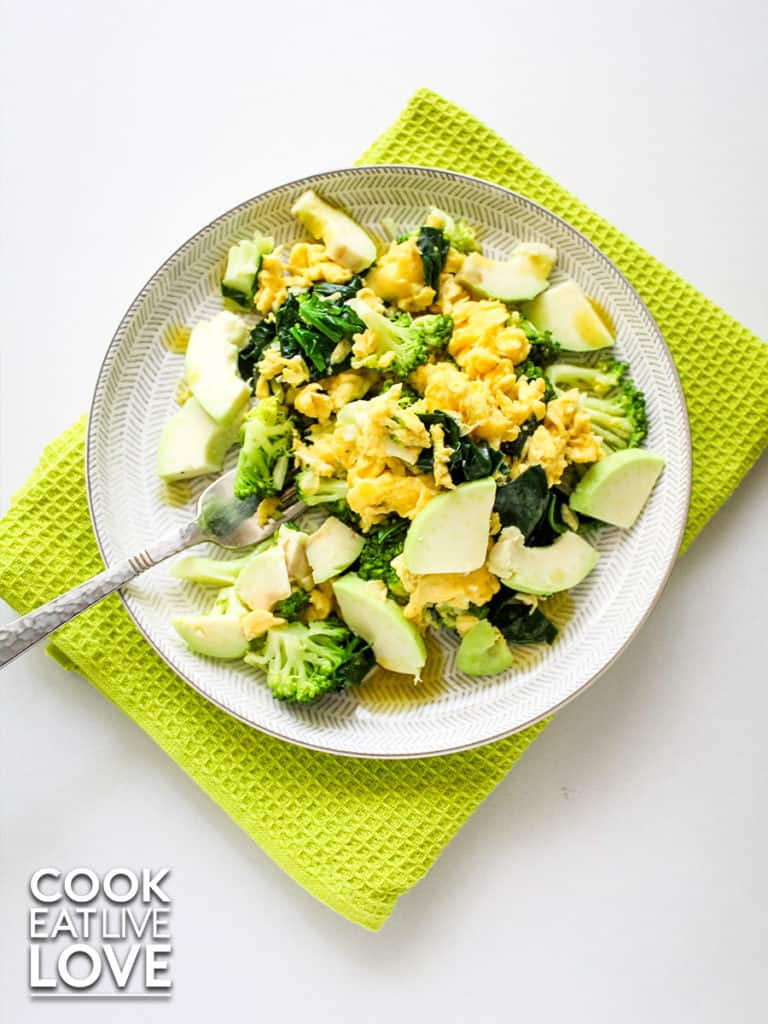 Plate of scrambled eggs with veggies pictured from overhead on a white background and lime green tea towel.  Fork in plate to scoop up a bite.