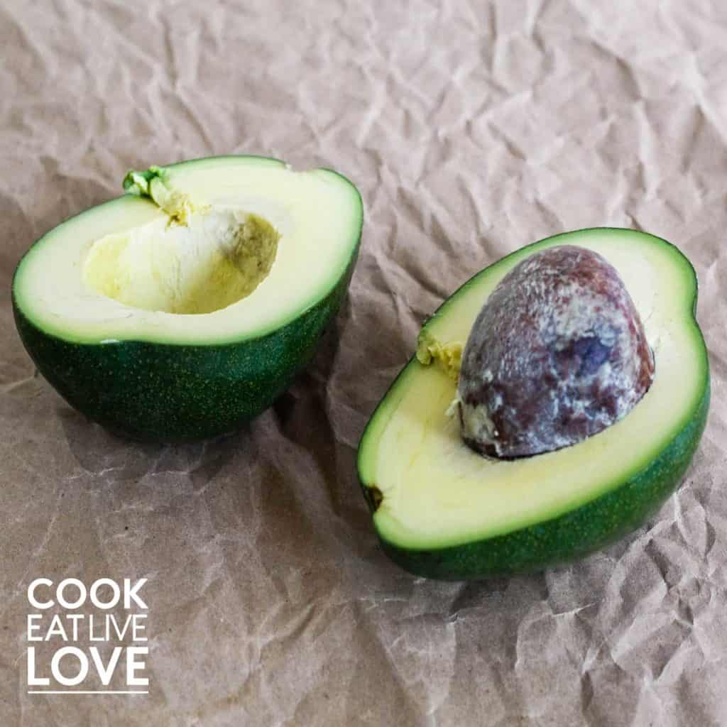 Avocado cut in half and sitting on crumbled brown paper surface.