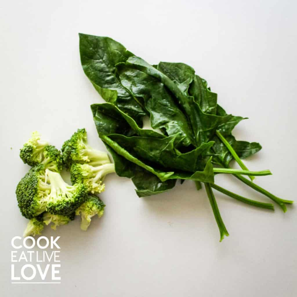 Fresh spinach and fresh broccoli for a egg veggie scramble on a white background.