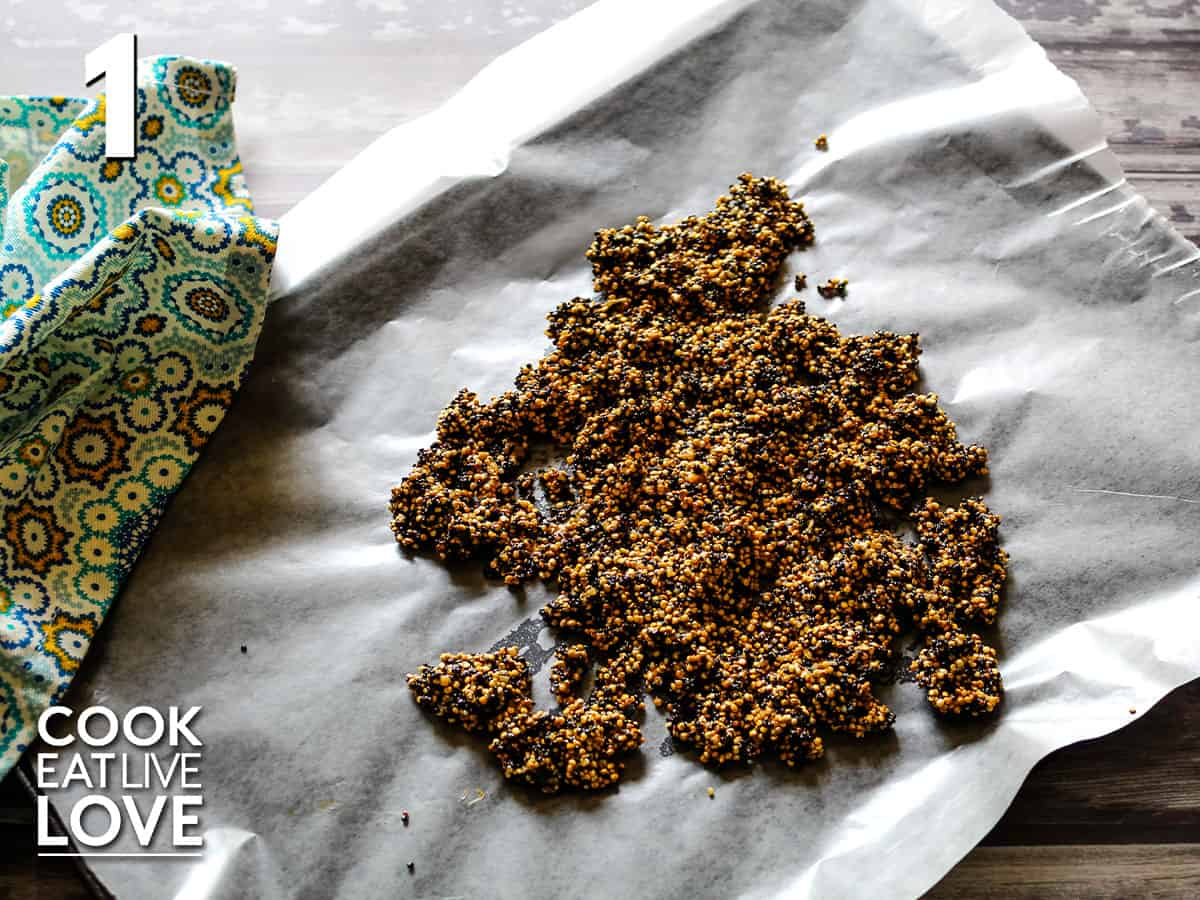 Caramelized quinoa is on a lined baking sheet cooling.