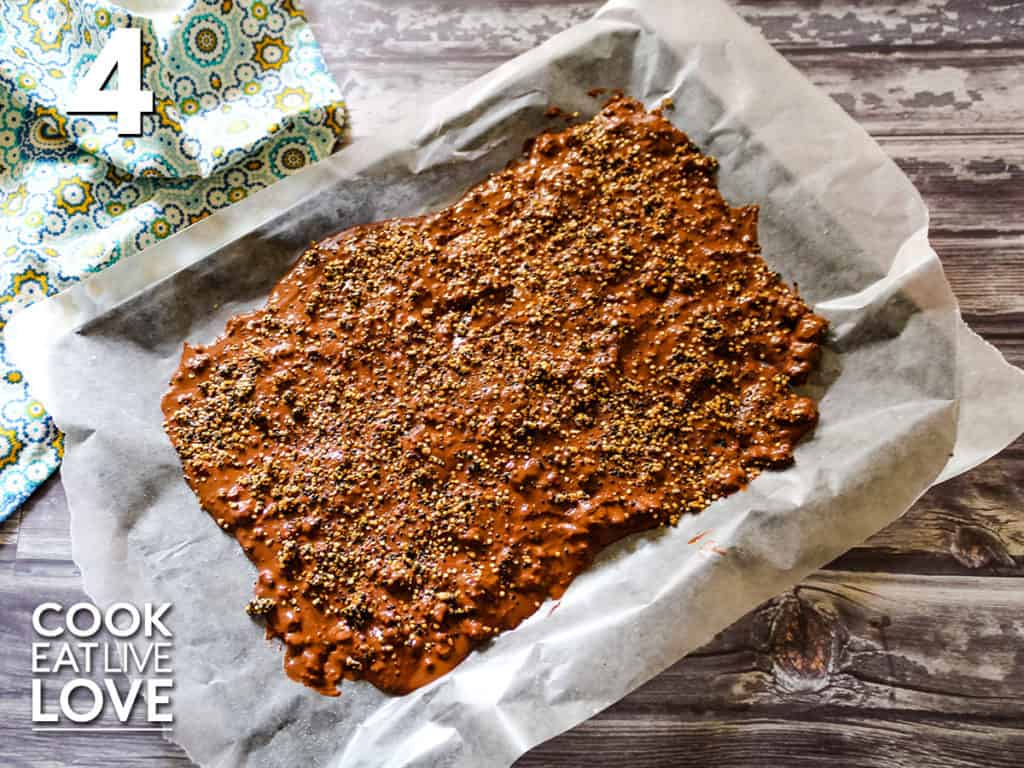Quinoa chocolate is spread out on a baking sheet and topped with caramelized quinoa and sea salt.