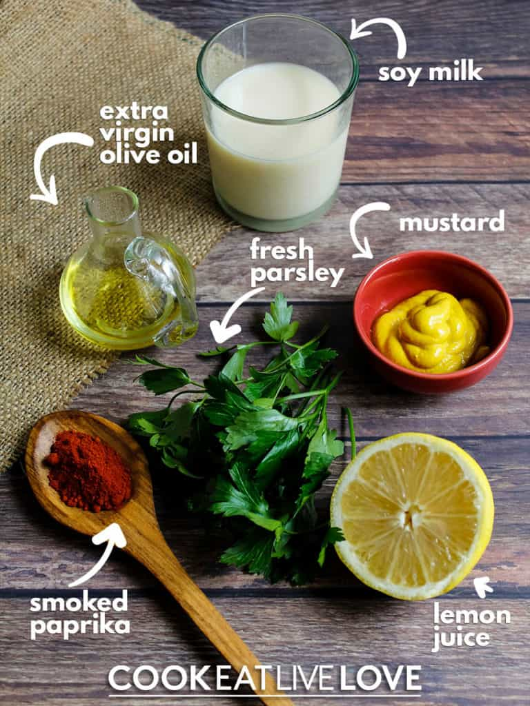 Front high angle photo of ingredients for smoked paprika mayo:  soy milk, mustard, fresh parsley, lemon juice, smoked paprika, extra virgin olive oil