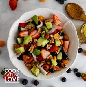 Overhead of summer berry salad in white bowl with wooden spoon to top left of bowl along with dressing. Berries on the counter around the bowl.