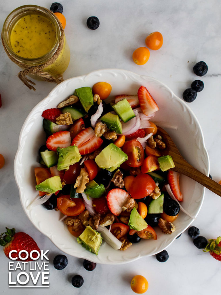 Overhead photo of summer berry salad in white bowl with wooden spoon in bowl.  Fresh berries are on the surface of the counter around the bowl and a jar of dressing is in the top left corner.