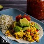 Blue plate with tofu scramble taco and avocado.