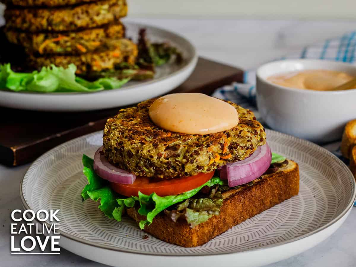 Open face sandwich with quinoa burger and sauce on top.