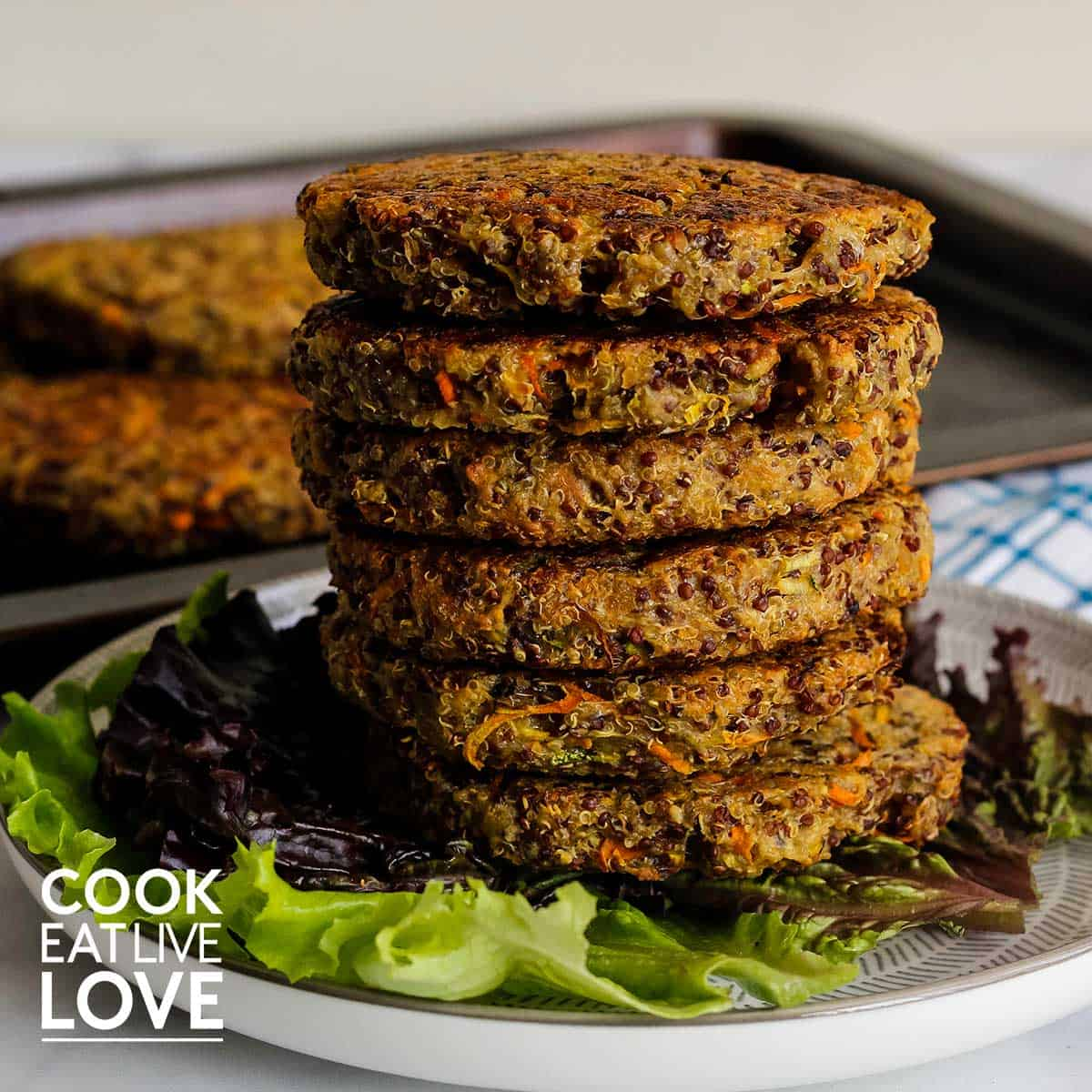 Stack of quinoa burgers on a plate with leaf lettuce.
