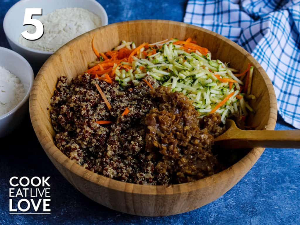 Wooden bowl is shown with cooked quinoa, cooked onion, shredded carrots and zucchini.