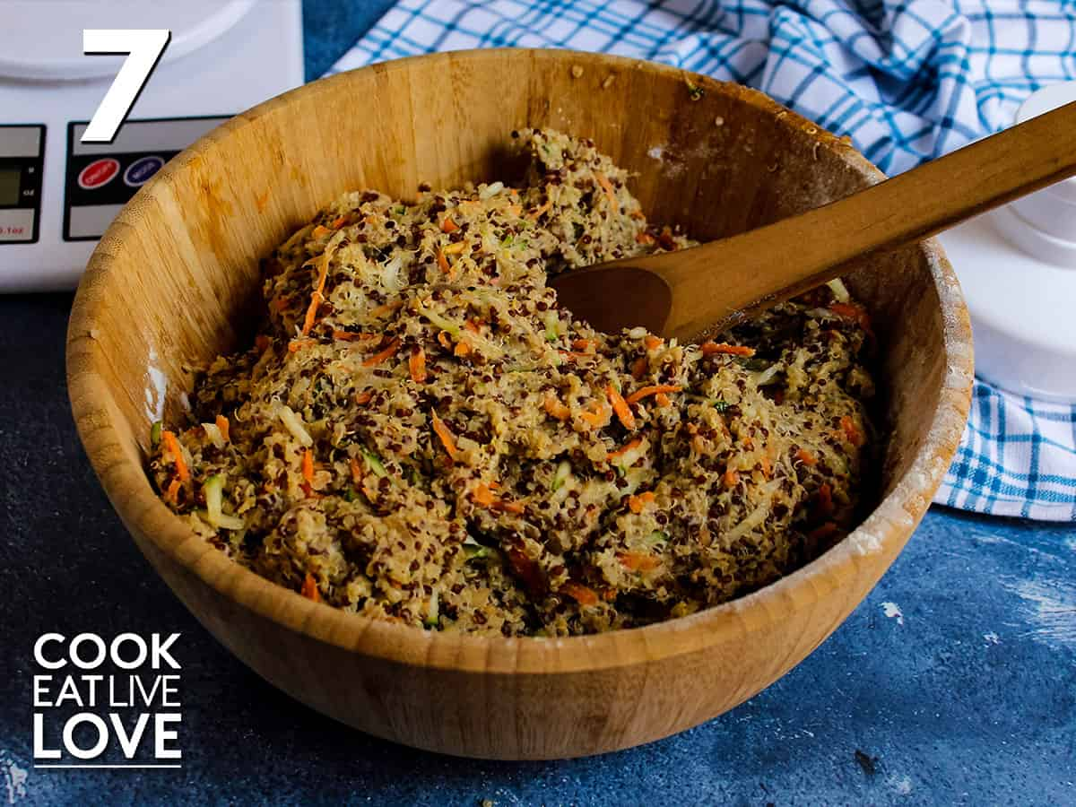 Quinoa mixture is fully mixed in wooden bowl with a wooden spoon on the side.