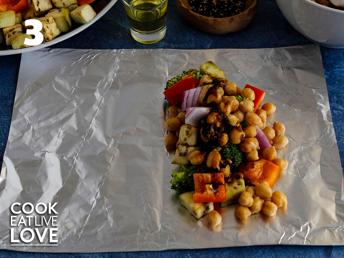 Chickpeas added to veggies on top of sheet of foil