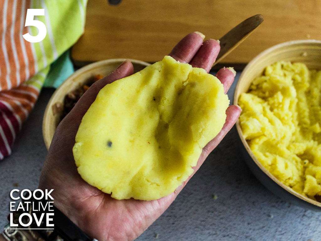 Hand filled with flattened potatoes to demonstrate how to begin shaping the stuffed papa rellena.