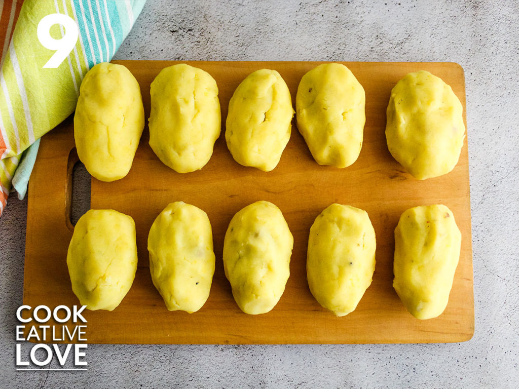 Shaped papa rellena are shown on a wooden cutting board lined up ready to cook.