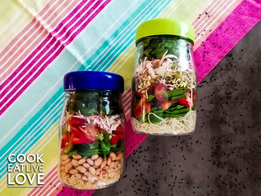 Two asian salads in jars ready to take with you on a gray back ground with bright colored material and some black sesame seeds.