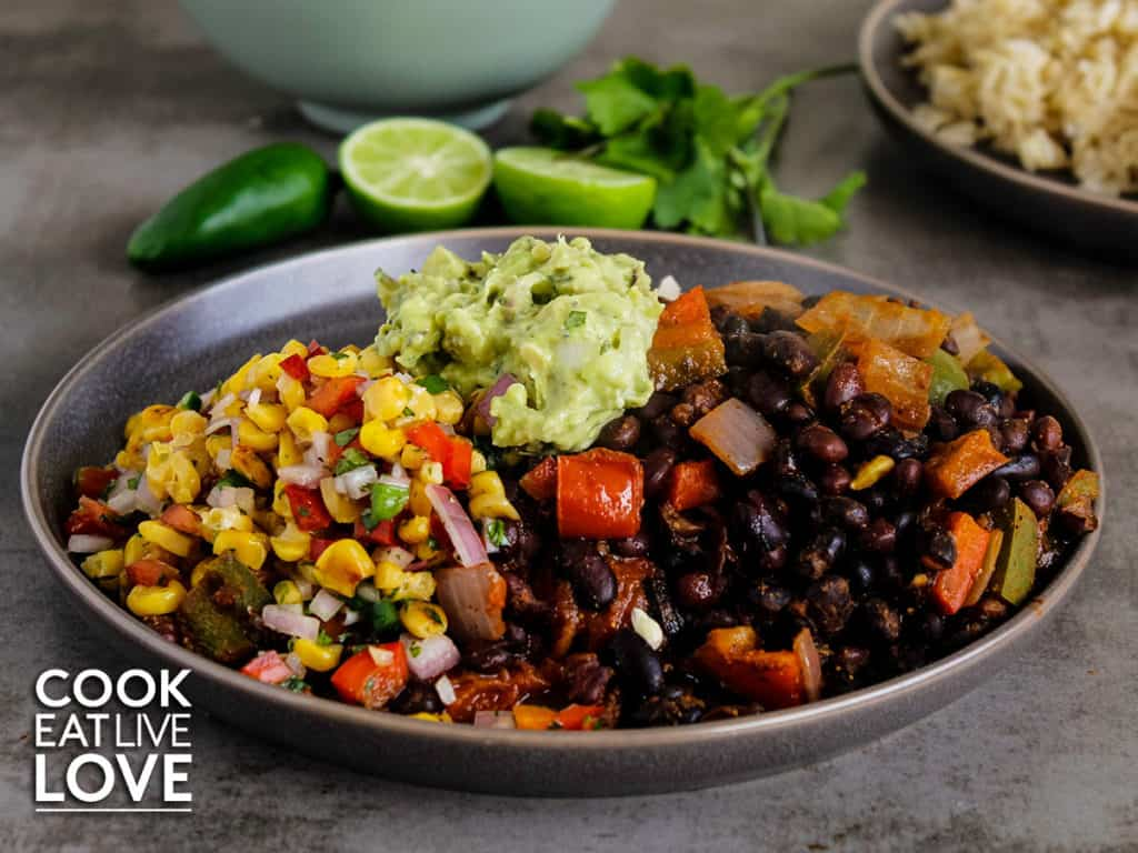 Front view of plate with black bean bake served up alongside roasted corn salsa.  Plate is topped with some guacamole.