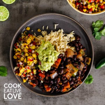 Overhead view of plate of black bean bake with roasted corn salsa topped with guacamole served over rice. Limes, cilantro, jalapeno and a bowl of frame salad are around the plate.