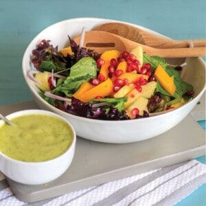 Mango avocado salad in a bowl with dressing on the side