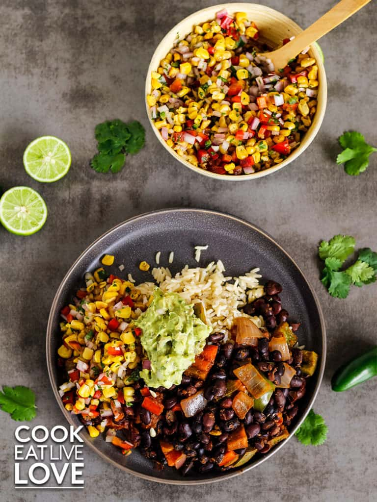 Overhead view of final plate with gray-brown plate with black beans, roasted corn salsa served with rice and topped with guacamole.  Above is a bowl with roasted corn salsa and around the dishes are cilantro, whole jalapenos and limes.