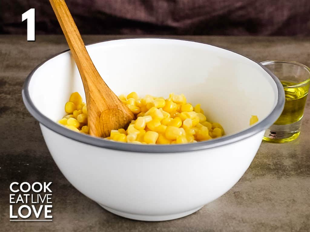 Bowl with corn and spoon.  Olive oil is in the back and will soon be added to bowl.