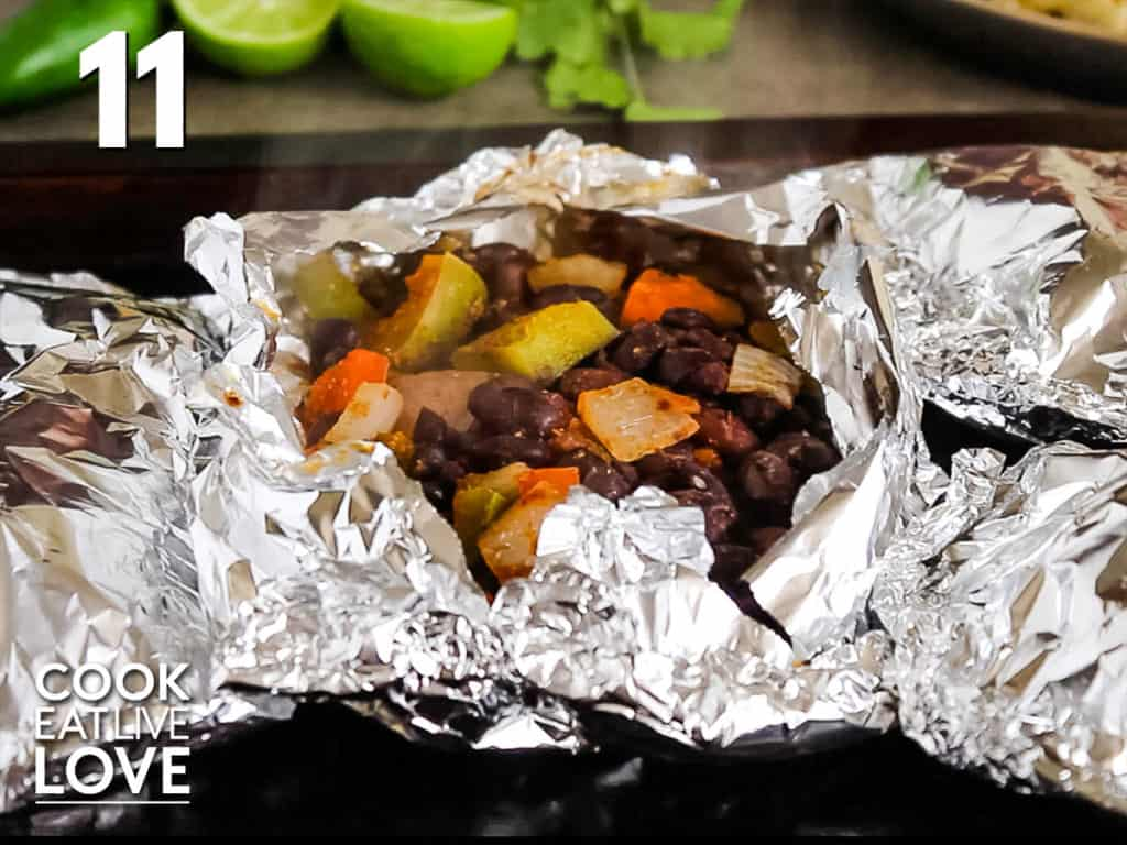 Cut open cooked package on baking tray with other packets showing the cooked black beans and veggies.